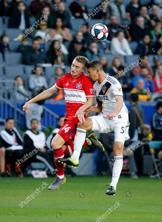 Chicago Fire midfielder Djordje Mihailovic (14), and LA Galaxy defender Daniel Steres (5), battle for the ball during an MLS soccer match between LA Galaxy and Chicago Fire in Carson, Calif., . The Galaxy won 2-1