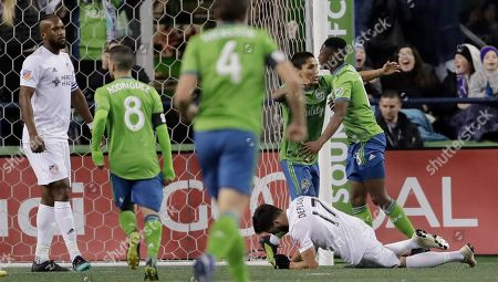 Seattle Sounders' Kelvin Leerdam, right, is hugged by forward Raul Ruidiaz, second from right, after Leerdam scored a goal against FC Cincinnati during the first half of an MLS soccer match, in Seattle