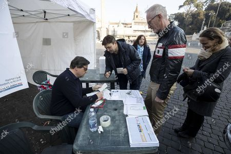 Former Italian Economic Development Minister Carlo Calenda (L) hands out ballots to voters at a PD party tent during the primary elections for the national secretariat of the Italian Democratic Party (Partito Democratico, PD), in Rome, Italy, 03 March 2019. PD politicians Maurizio Martina, who replaced Renzi following his resignation in 2018, Roberto Giachetti and Nicola Zingaretti are the main candidates for the Democratic Party's leadership election which was triggered by the party's general election defeat and Renzi's withdrawal in 2018.