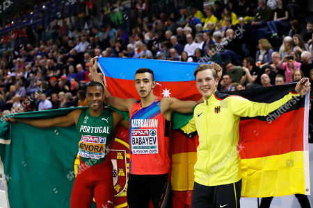 Silver medalist Nelson Evora of Portugal, gold medalist Nazim Babayev of Azerbaijan and bronze medalist Max Hess of Germany, from left to right, celebrate after the men's triple jump final at the European Athletics Indoor Championships at the Emirates Arena in Glasgow, Scotland