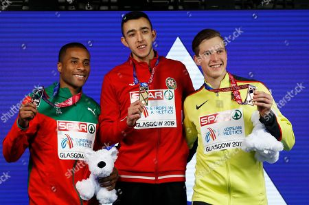 Silver medalist Nelson Evora of Portugal, gold medalist Nazim Babayev of Azerbaijan and bronze medalist Max Hess of Germany, from left to right, pose on the podium of the men's triple jump final at the European Athletics Indoor Championships at the Emirates Arena in Glasgow, Scotland