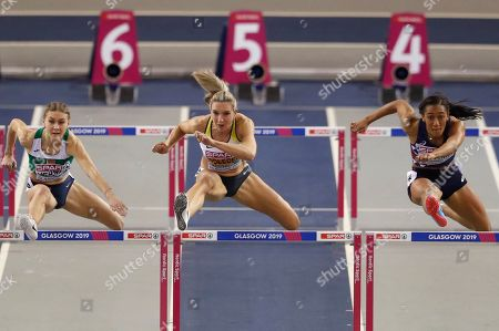 Belarus' Elvira Herman, left, Germany's Cindy Roleder, center, and France's Solene Ndama, right, compete in a semifinal of the women's 60 meters hurdles race during the European Athletics Indoor Championships at the Emirates Arena in Glasgow, Scotland