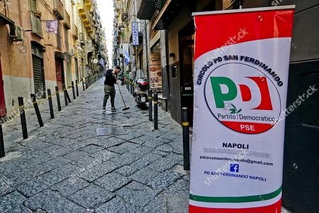 A man cleans the pavement in front of his shop while a 'Partito Democratico' (PD) poster indicates the location of a polling station for the primary elections for the national secretariat of the Italian Democratic Party (PD), in Naples, Italy, 03 March 2019. PD politicians Maurizio Martina, who replaced Renzi following his resignation in 2018, Roberto Giachetti and Nicola Zingaretti are the main candidates for the Democratic Party's leadership election which was triggered by the party's general election defeat and Renzi's withdrawal in 2018.