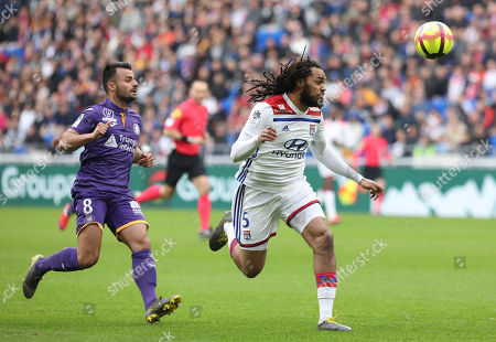 Lyon defender Jason Denayer, right, and Toulouse's Corentin Jean challenge for the ball during the French League One soccer match between Lyon and Toulouse, in Decines, near Lyon, central France