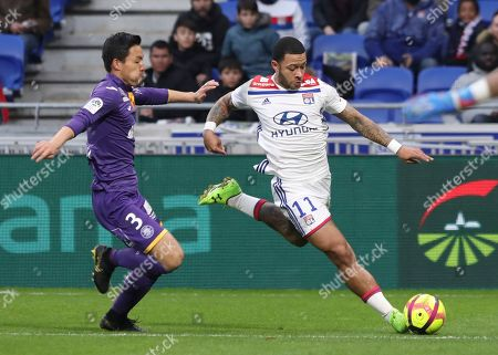 Lyon forward Memphis Depay, right, and Toulouse's Gen Shoji challenge for the ball during the French League One soccer match between Lyon and Toulouse, in Decines, near Lyon, central France