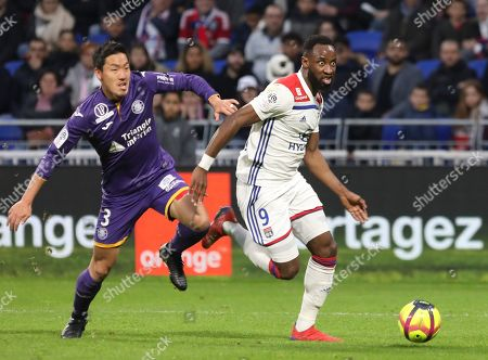 Lyon forward Moussa Dembele, right, and Toulouse's Gen Shoji challenge for the ball during the French League One soccer match between Lyon and Toulouse, in Decines, near Lyon, central France