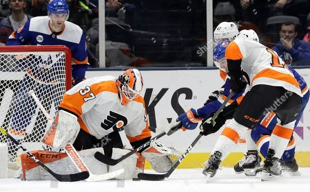 Stock Photo of Adam Pelech, Brian Elliott, Corban Knight, Andrew MacDonald. New York Islanders defenseman Adam Pelech (3) advances the puck in front of Philadelphia Flyers goaltender Brian Elliott (37) before scoring a goal with Flyers center Corban Knight (10) and Flyers defenseman Andrew MacDonald (47) defending during the third period of an NHL hockey game, in Uniondale, N.Y. The Flyers defeated the Islanders 4-1