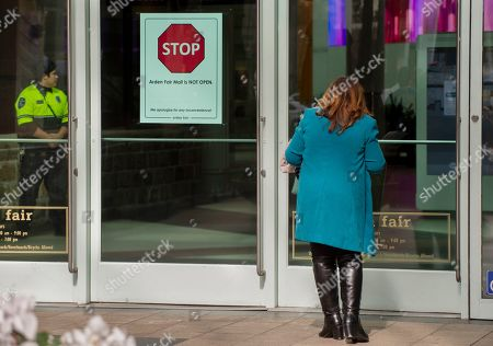 Shopper Maria Barajas, of Fresno, Calif., peers into the entrance door to the Arden Fair Mall in Sacramento, . The mall closed Sunday in anticipation of potential disruptions following yesterday's announcement by Sacramento District Attorney Anne Marie Schubert that the two officers who shot and killed Stephon Clark last year will not be charged for the shooting