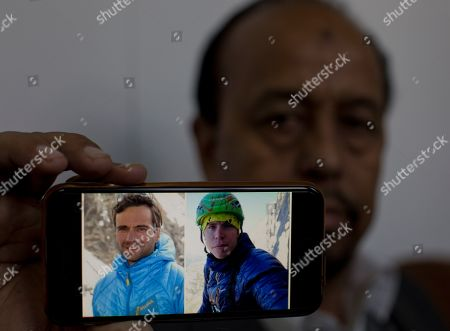 Karrar Haidri, secretary of the Alpine Club of Pakistan shows pictures of two missing climbers, Briton Tom Ballard, right, and Italian Daniele Nardi in Islamabad, Pakistan, . Pakistani military helicopters took off Monday with four Spanish rescuers to search for a missing pair of European climbers on Nanga Parbat, the world's ninth highest mountain