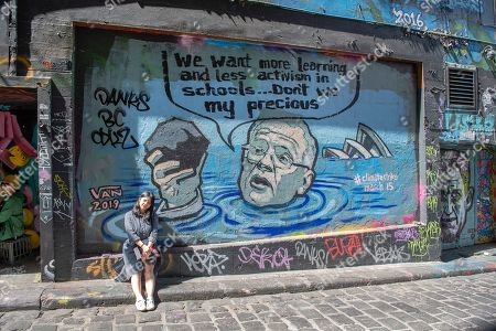 A person poses for a photograph with a mural depicting Australian Prime Minister Scott Morrison in a flooded Sydney harbour holding a lump of coal, in Hosier Lane in Melbourne, Victoria, Australia, 04 March 2019. The mural was painted by artist Van T Rudd, the nephew of former prime minister Kevin Rudd.