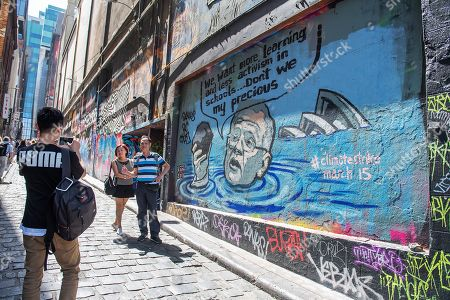 People pose for a photograph with a mural depicting Australian Prime Minister Scott Morrison in a flooded Sydney harbour holding a lump of coal, in Hosier Lane in Melbourne, Victoria, Australia, 04 March 2019. The mural was painted by artist Van T Rudd, the nephew of former prime minister Kevin Rudd.