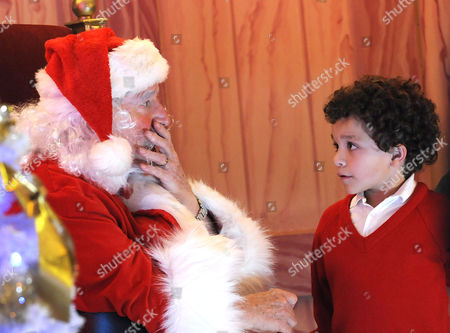 Stock Image of Ken Barlow, played by William Roache, dressed as Santa Claus with grandson Simon, played by Alex Bain, arrives with maternal grandfather George, played by Anthony Valentine.