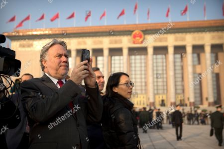 Stock Picture of Greek Foreign Minister George Katrougalos, left, takes a cellphone photo outside the Great Hall of the People before the opening session of China's National People's Congress (NPC) in Beijing, . China's government announced a robust annual economic growth target and a 7.5 percent rise in military spending Tuesday at a legislative session overshadowed by a tariff war with Washington
