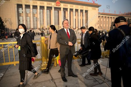 Greek Foreign Minister George Katrougalos, center, stands outside the Great Hall of the People before the opening session of China's National People's Congress (NPC) in Beijing, . China's government announced a robust annual economic growth target and a 7.5 percent rise in military spending Tuesday at a legislative session overshadowed by a tariff war with Washington