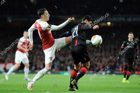 Mesut Ozil of Arsenal and Benjamin Andre of Stade Rennais F.C  in action during the UEFA Europa League round of 16 second leg match between Arsenal and Stade Rennais F.C at the Emirates Stadium in London, UK - 14th March 2019