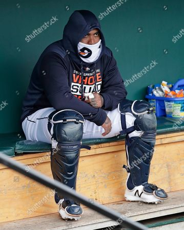 Detroit Tigers' Hector Sanchez bundles up in the dugout as temperatures dropped before the start of a spring training baseball game against the Toronto Blue Jays, in Lakeland, Fla