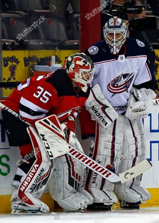 Columbus Blue Jackets goaltender Keith Kinkaid, right, talks with former teammate New Jersey Devils goaltender Cory Schneider, left during warm ups prior to their NHL hockey game, in Newark, N.J