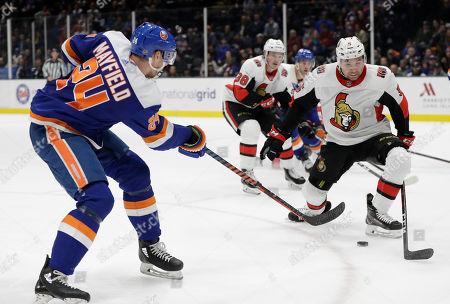Scott Mayfield, Cody Ceci. New York Islanders defenseman Scott Mayfield (24) shoots with Ottawa Senators defenseman Cody Ceci (5) defending during the second period of an NHL hockey game, in Uniondale, N.Y