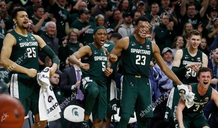 From left, Michigan State forward Kenny Goins (25), guard Cassius Winston (5), forward Xavier Tillman (23), guard Matt McQuaid (20) and guard Foster Loyer (3) react after a basket by guard Brock Washington (14) during the second half of an NCAA college basketball game against Nebraska, in East Lansing, Mich