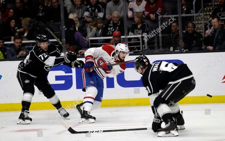 Phillip Danault, Tyler Toffoli, Sean Walker. Montreal Canadiens' Phillip Danault, center, shoots between Los Angeles Kings' Tyler Toffoli (73) and Sean Walker (61) during the first period of an NHL hockey game, in Los Angeles