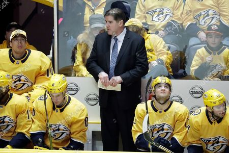 Nashville Predators head coach Peter Laviolette watches from the bench in the third period of an NHL hockey game between the Predators and the Minnesota Wild, in Nashville, Tenn