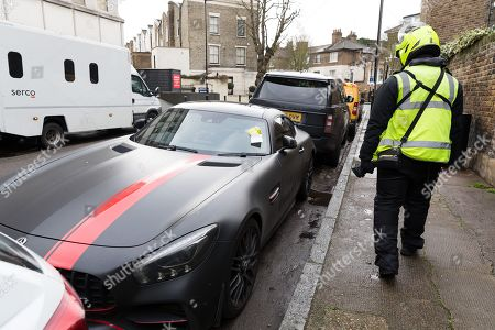 A traffic warden walks past Stoke City footballer, Saido Berahino's car after giving it a parking ticket outside Highbury Corner Magistrates court.