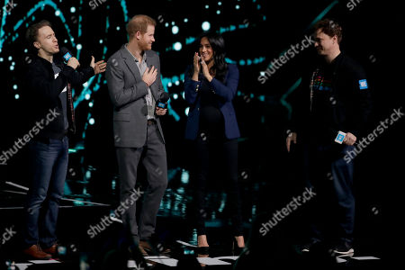 Meghan Meghan Duchess of Sussex, applauds as she is brought on stage by Prince Harry at the end of his speech with WE Day founders, Canadian brothers Craig, left, and Marc Kielburger at WE Day UK, a global initiative to encourage young people to take part in positive social change at the SSE Arena in Wembley, London