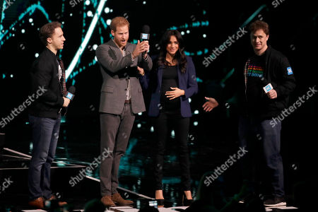 Meghan Meghan Duchess of Sussex, applauds is brought on stage by Prince Harry at the end of his speech with WE Day founders, Canadian brothers Craig, left, and Marc Kielburger at WE Day UK, a global initiative to encourage young people to take part in positive social change at the SSE Arena in Wembley, London