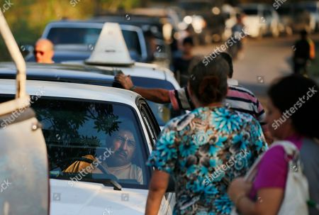 Jose Perez waits in his car to fill up his tank at a gas station in San Cristobal, Venezuela. Perez said he expected to wait up to 24 hours, for gasoline that's nearly free in socialist Venezuela