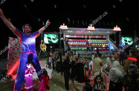A Pakistani child stands next to cut-out of Pakistan's former captain Shahid Afridi in Karachi, Pakistan, . Giant cut-outs of players have been put on display on main streets of Karachi which hosts the last leg of eight Pakistan Super League Twenty20 matches from next Saturday