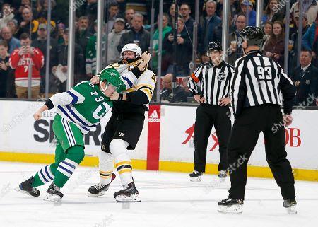 Linesman Brian Murphy (93) and referee Kendrick Nicholson watch as Carolina Hurricanes left wing Micheal Ferland (79) and Boston Bruins right wing David Backes (42) fight during the first period of an NHL hockey game, in Boston