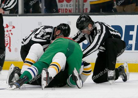 Linesman Ryan Daisy and Brian Murphy (93) break up a fight between Carolina Hurricanes left wing Micheal Ferland (79) and Boston Bruins right wing David Backes (42) during the first period of an NHL hockey game, in Boston