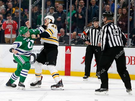 Stock Image of Linesman Brian Murphy (93) and referee Kendrick Nicholson watch as Carolina Hurricanes left wing Micheal Ferland (79) and Boston Bruins right wing David Backes (42) fight during the first period of an NHL hockey game, in Boston