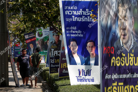 Pedestrians walk past electoral campaign posters including that of Thai Raksa Chart Party (2 R), portraying Thai Raksa Chart Party leader Preechapol Pongpanich (L) in Bangkok, Thailand, 07 March 2019. Thai Constitutional Court ordered the dissolution of Thai Raksa Chart Party for nominating Princess Ubolratana as its prime minister candidate for the general election. The court also decided to impose a political ban on 14 party executives for 10 years.