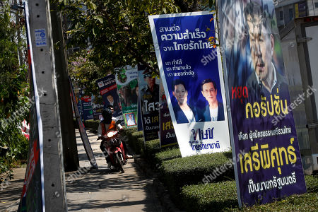 A motorcycle taxi rides on the sidewalk past electoral campaign posters including that of Thai Raksa Chart Party (2-R), portraying Thai Raksa Chart Party leader Preechapol Pongpanich (L) in Bangkok, Thailand, 07 March 2019. Thai Constitutional Court ordered the dissolution of Thai Raksa Chart Party for nominating Princess Ubolratana as its prime minister candidate for the general election. The court also decided to impose a political ban on 14 party executives for 10 years.