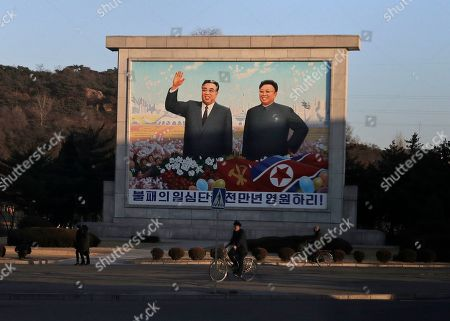 Men ride their bicycle past a mural of late North Korean leaders Kim Il Sung, left, and his son Kim Jong Il in Pyongyang, North Korea