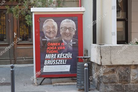 """A poster from a Hungarian government campaign showing EU Commission President Jean-Claude Juncker and Hungarian-American financier George Soros with the caption """"You, too, have a right to know what Brussels is preparing to do"""" is displayed on a phone booth in Budapest, . Hungarian officials said the campaign claiming that EU leaders like Juncker, backed by Soros, want to bring mass migration into Europe, would end by March 15"""