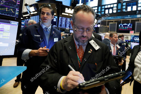Robert Arciero, center, works with fellow traders on the floor of the New York Stock Exchange, . U.S. stocks moved lower in morning trading, led by banks and technology companies, putting the market on track for its first losing week since January