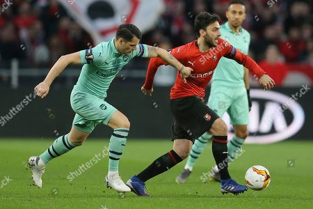 Renne's Benjamin Andre, right, and Arsenal midfielder Granit Xhaka challenge for the ball during the Europa League round of 16, first leg soccer match between Rennes and Arsenal at Roazhon Park in Rennes, northwestern France