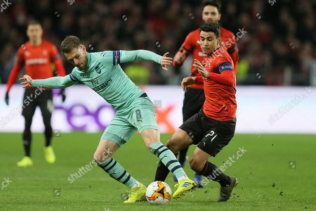 Arsenal's Aaron Ramsey, left, and Rennes' Benjamin Andre fight for the ball during the Europa League round of 16, first leg soccer match between Rennes and Arsenal at Roazhon Park in Rennes, northwestern France