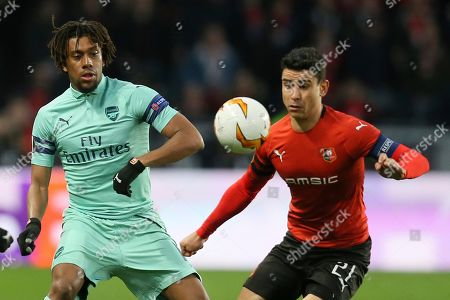 Arsenal's Alex Iwobi, left, and Rennes' Benjamin Andre go for the ball during the Europa League round of 16, first leg soccer match between Rennes and Arsenal at Roazhon Park in Rennes, northwestern France