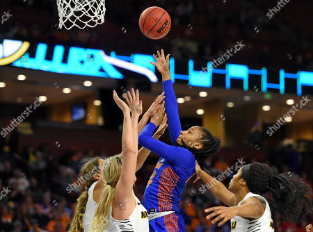 Florida's Paige Robinson shoots over Missouri's Hannah Schuchts, left, Sophie Cunningham, center and Emmanuelle Tahane during the first half of a Southeastern Conference NCAA college basketball tournament game, in Greenville, S.C