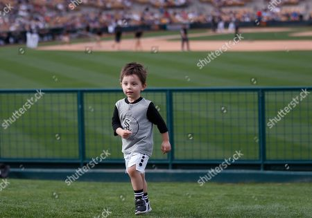 Three-year-old Greyson Johnson, son of Chicago White Sox infielder Chris Johnson, runs up a hill in the lawn seating area during a spring training baseball game between the Milwaukee Brewers and the White Sox, in Glendale, Ariz