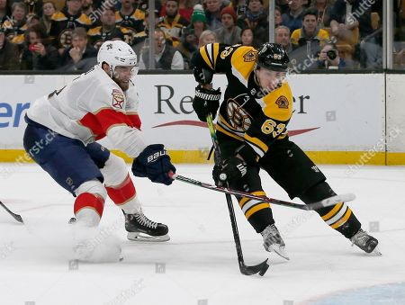Florida Panthers defenseman Aaron Ekblad (5) breaks up a shot-attempt by Boston Bruins left wing Brad Marchand (63) during the second period of an NHL hockey game, in Boston