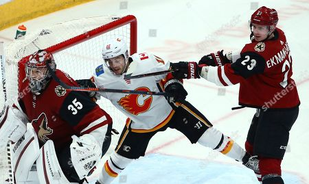 Arizona Coyotes defenseman Oliver Ekman-Larsson (23) shoves Calgary Flames center Derek Ryan (10) as Coyotes goaltender Darcy Kuemper (35) watches the puck during the third period of an NHL hockey game, in Glendale, Ariz. The Coyotes won 2-0