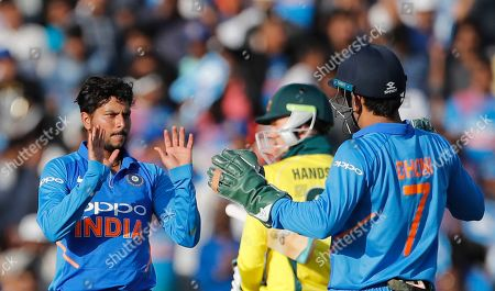 Kuleep Yadav, Mahendra Singh Dhoni, Peter Handscomb. India's Kuleep Yadav, left, celebrates with teammate Mahendra Singh Dhoni, right, the dismissal of Australia's Peter Handscomb, center, during the third one day international cricket match between India and Australia in Ranchi, India