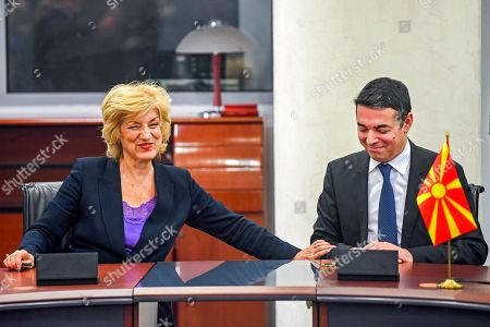 Greece's Alternate Foreign Minister Sia Anagnostopoulou   (L) touches North Macedonian Foreign Minister Nikola Dimitrov (R) as they are signing the agreement to open a new border crossing between Greece and North Macedonia in Skopje