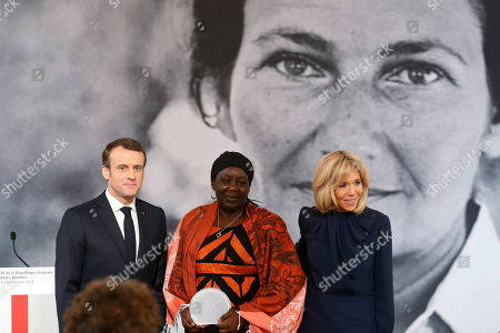 France's President Emmanuel Macron, left, Cameroonian activist Aissa Doumara Ngatansou, center and Brigitte Trogneux pose at the end of the Simone Veil prize presentation, at the Elysee Palace, in Paris,. France's first Simone Veil prize goes to a Cameroonian activist Aissa Doumara Ngatansou who has worked against forced marriages and other violence against girls and women