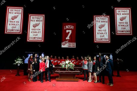 Family members pose with the casket of former Detroit Red Wings player Ted Lindsay before a public viewing, in Detroit. Lindsay pioneered the first NHL hockey players' union despite intense opposition from team management, began the tradition of taking the Stanley Cup closer to fans by skating it around the ice and refused to attend his own Hall of Fame induction ceremony because only men were allowed. Lindsay died Monday at the age of 93