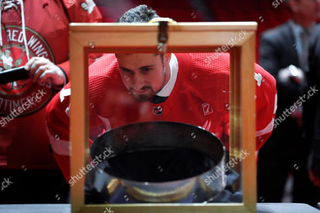 Detroit Red Wings center Dylan Larkin views a ring off the Stanley Cup during the public viewing of former Detroit Red Wings player Ted Lindsay, in Detroit. Lindsay pioneered the first NHL hockey players' union despite intense opposition from team management, began the tradition of taking the Stanley Cup closer to fans by skating it around the ice and refused to attend his own Hall of Fame induction ceremony because only men were allowed. Lindsay died Monday at the age of 93